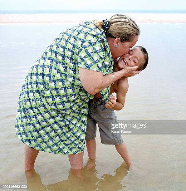 mature woman and boy (5-7) on beach, woman kissing boy on cheek - dicke frauen am strand stock-fotos und bilder