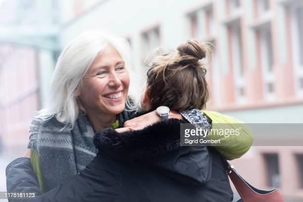 mature woman and daughter hugging on city street - sigrid gombert stock-fotos und bilder