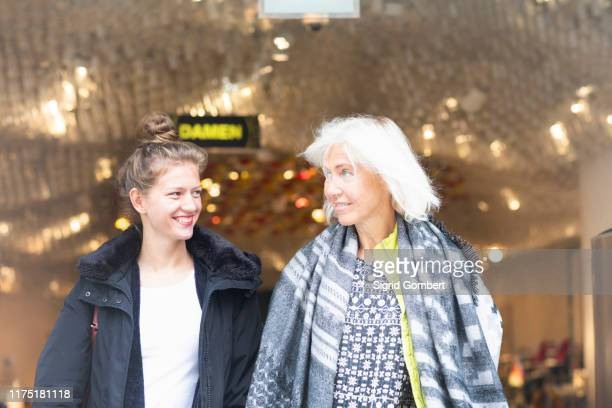 mature woman and daughter leaving shop in city - sigrid gombert stock pictures, royalty-free photos & images