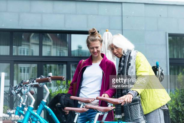 mature woman and daughter looking at city bicycles at bike park - sigrid gombert stock pictures, royalty-free photos & images