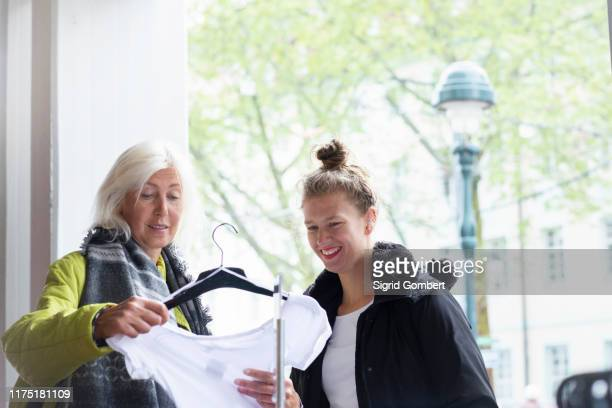 mature woman and daughter looking at t-shirt in shop - sigrid gombert stock pictures, royalty-free photos & images