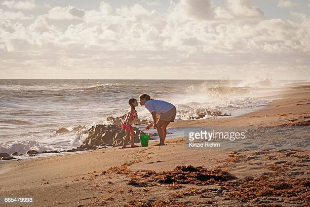 mature woman and daughter puckering for a kiss on beach, blowing rocks preserve, jupiter island, florida, usa - jupiter island stock photos and pictures
