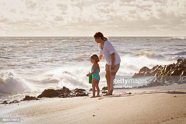 mature woman and daughter watching splashing waves, blowing rocks preserve, jupiter island, florida, usa - blowing rocks preserve stock photos and pictures