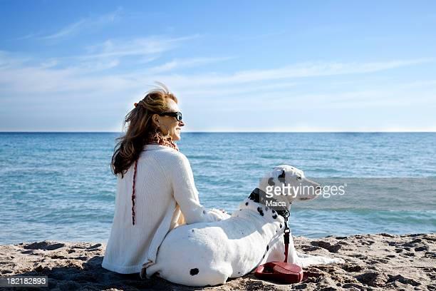 Mature femme et chien à la plage