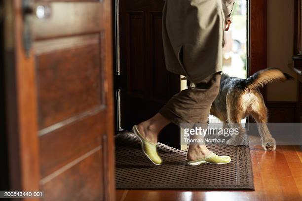 mature woman and dog walking out front door, rear view, low section - human doormat foto e immagini stock