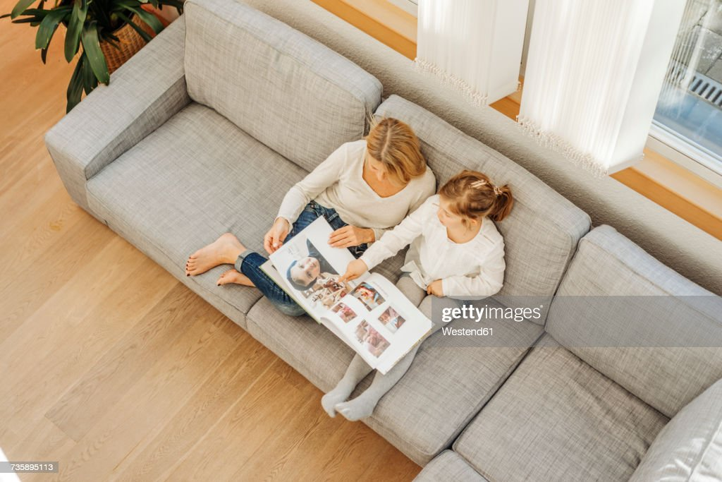 Mature woman and girl at home looking at photo album on couch : Stock Photo