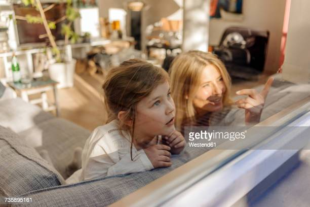 Mature woman and girl at home on couch looking out of window