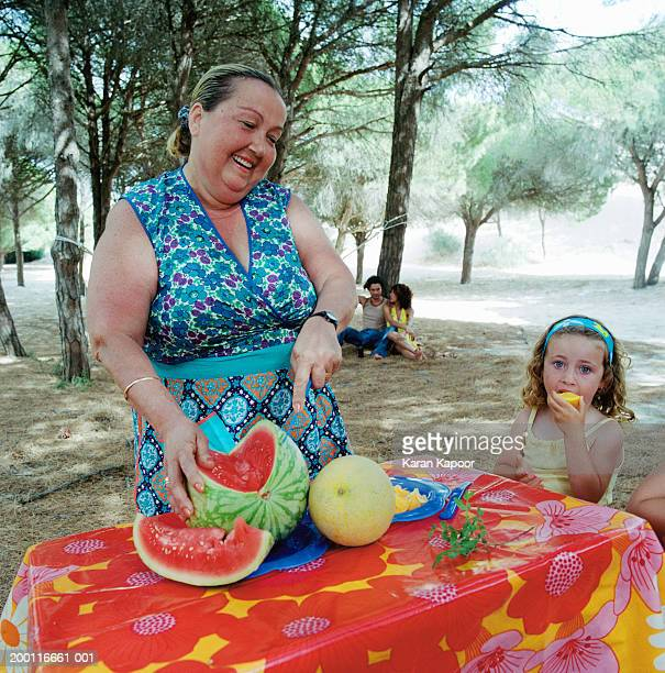 Mature woman and girl (2-4) at table outdoors, woman cutting melon