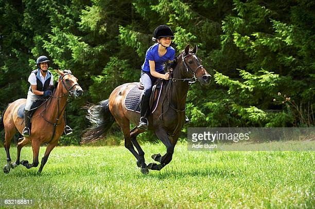 Mature woman and girl galloping on horse