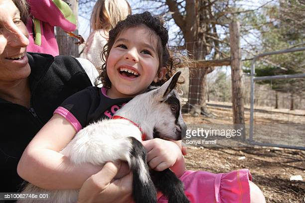 Mature woman and girl (4-5) with baby goat, laughing, outdoors