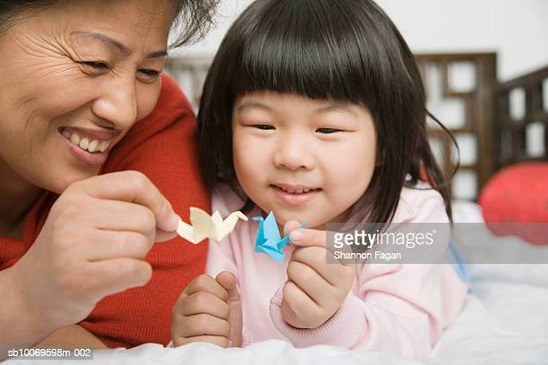 Mature woman and granddaughter (4-5) playing with Origami birds
