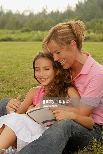 Mature woman and her daughter sitting in the park
