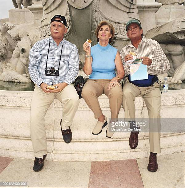 Mature woman and mature men eating sandwiches at edge of monument