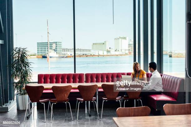 mature woman and mid adult man sitting at table and using laptop - mid adult men stock pictures, royalty-free photos & images
