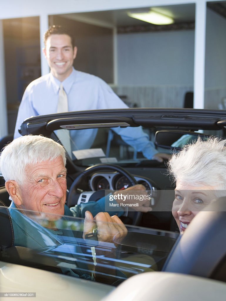 Mature woman and senior man in convertible at car dealership : Foto stock