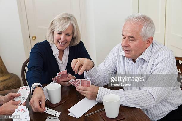 Mature woman and senior man playing cards