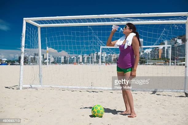 mature woman and soccer ball on copacabana beach, rio de janeiro, brazil - strand von copacabana stock-fotos und bilder