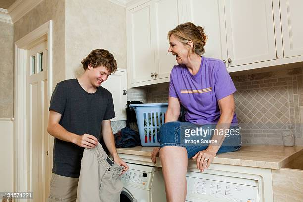 Mature woman and son in laundry room