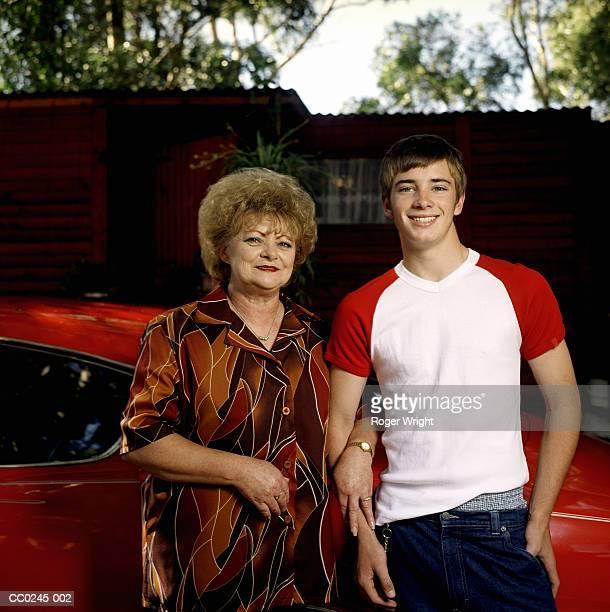 Mature woman and teenage boy (14-16) beside car, portrait
