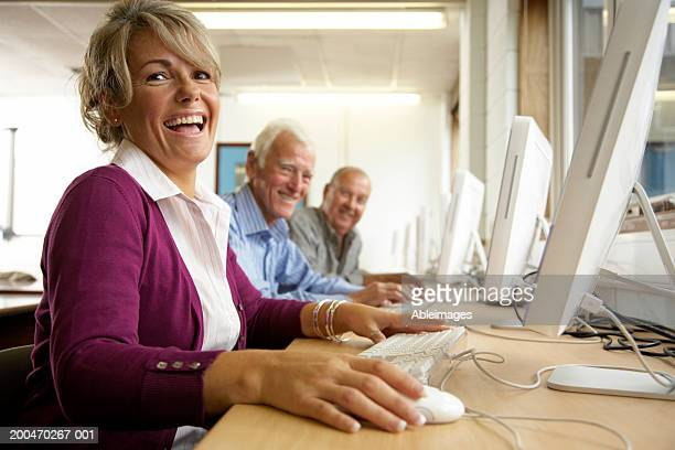 'Mature woman and two mature men in computing class, portrait'