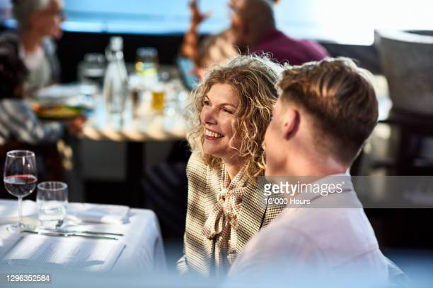 mature woman and young man in restaurant - restaurant stock pictures, royalty-free photos & images