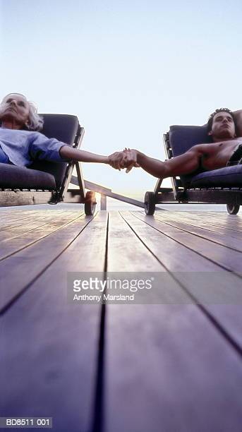 mature woman and young man on sun loungers holding hands - femme cougar photos et images de collection