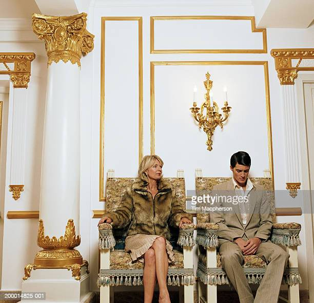 mature woman and young man sitting on chairs side by side - cougar woman fotografías e imágenes de stock