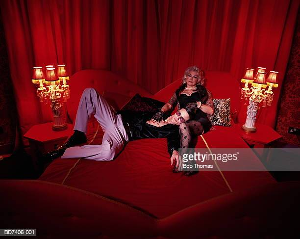 mature woman and younger man reclining on bed, portrait - cougar woman stock photos and pictures