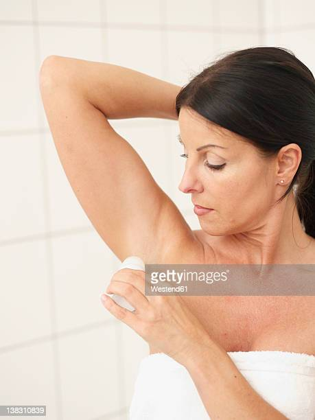 Mature woman applying deodorant on underarms