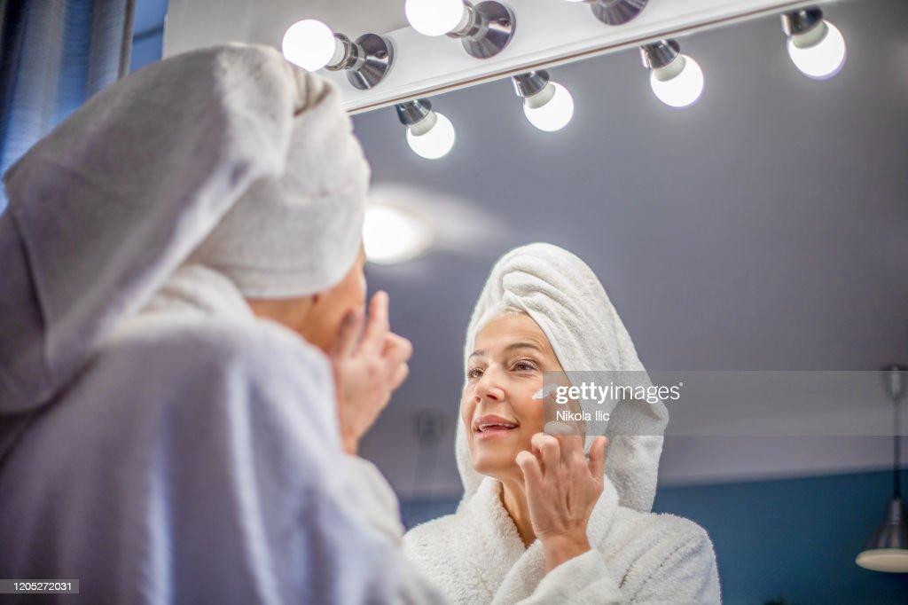 Rijpe vrouw die gezichtsroom toepast. : Stockfoto