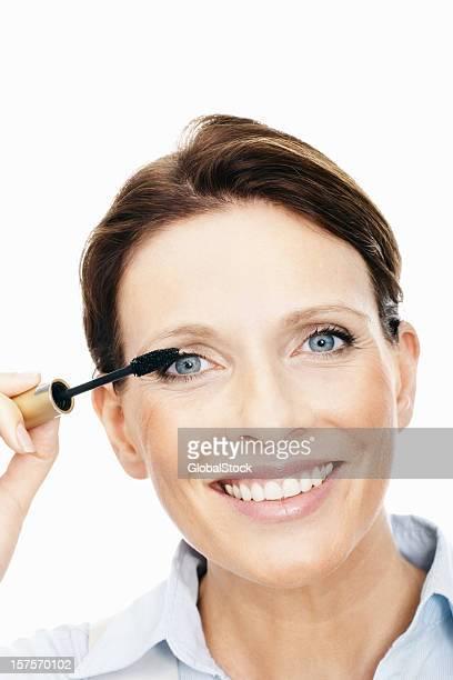 Mature woman applying mascara