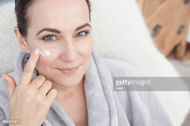 Mature woman applying moisturiser to face
