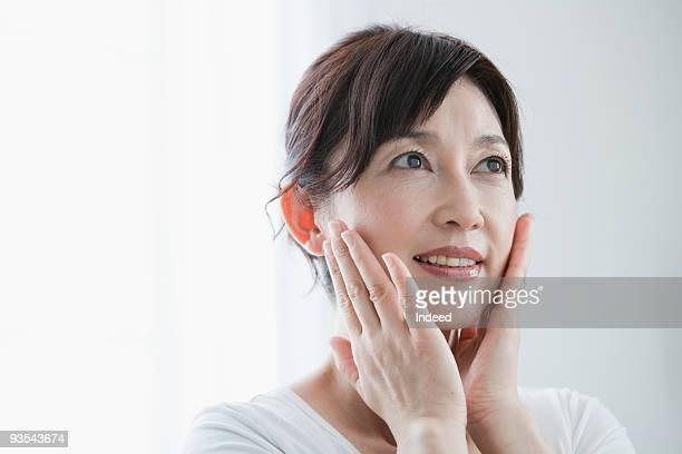 mature woman applying moisturizer to face - 美容 ストックフォトと画像