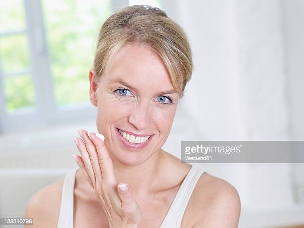 Mature woman applying moisturizer tube, smiling, portrait