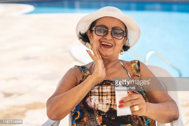 mature woman applying suntan lotion - uv protection stock pictures, royalty-free photos & images