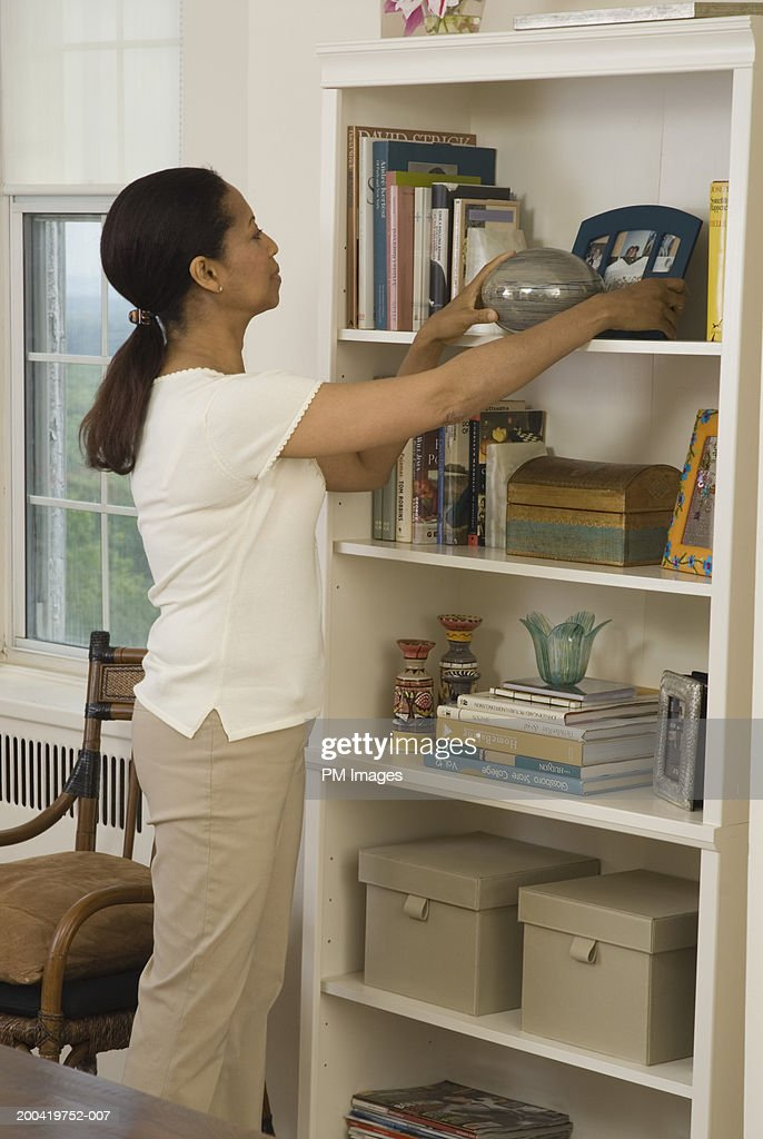 Mature woman arranging bookshelf, side view : Stock Photo