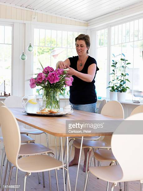 Mature woman arranging flowers on kitchen table