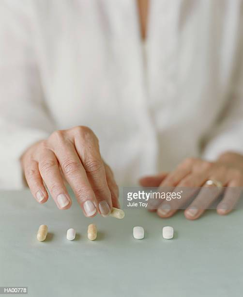 mature woman arranging pills on table - medium group of objects stock pictures, royalty-free photos & images