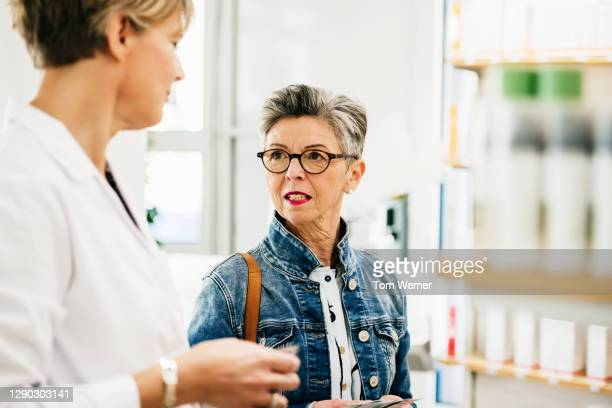 mature woman asking advice from chemist in pharmacy - german short haired pointer stock pictures, royalty-free photos & images