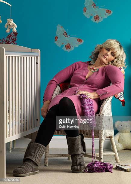 Mature woman asleep in chair next to cot