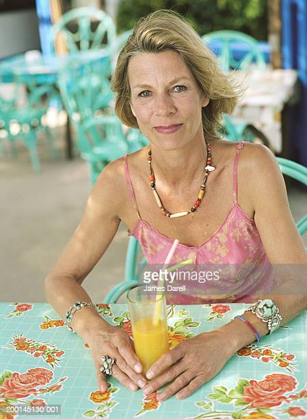 Mature woman at cafe table, holding glass of orange juice, portrait