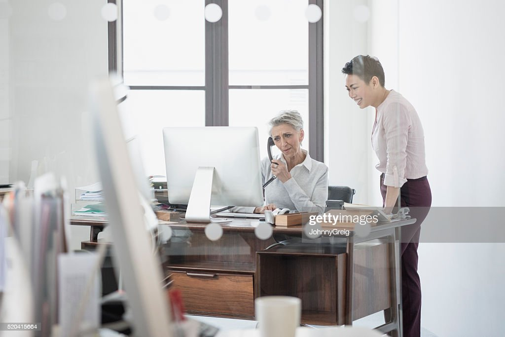 Mature woman at desk on phone with female colleague : Stock Photo