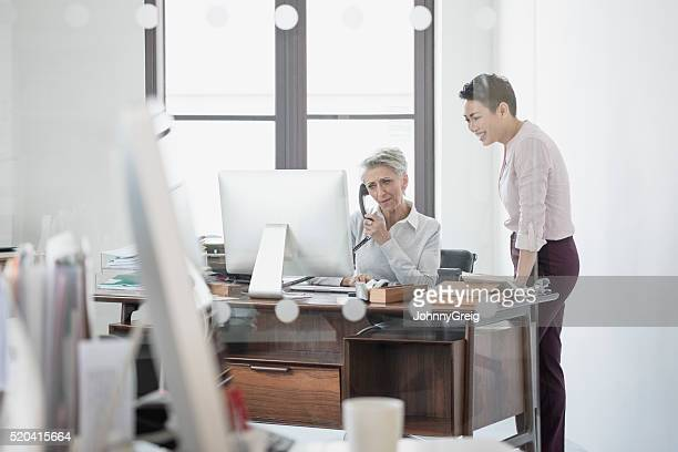 Mature woman at desk on phone with female colleague