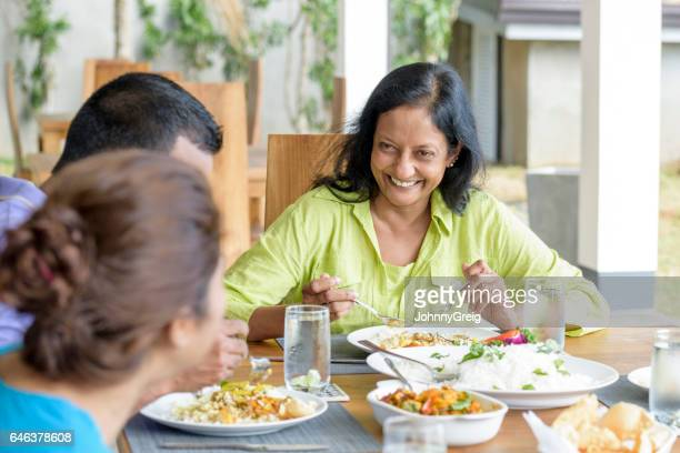 mature woman at dinner table with family - sri lankan culture stock pictures, royalty-free photos & images