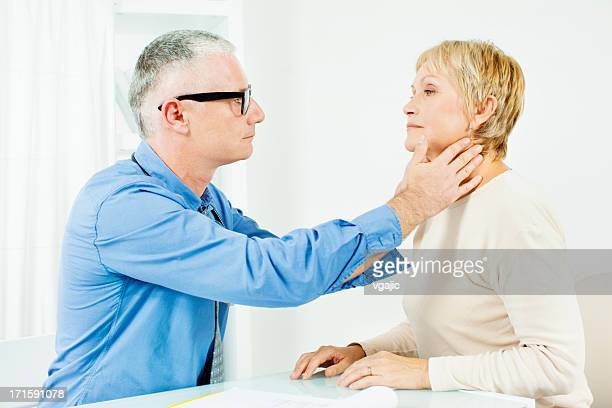 mature woman at doctors office. - tonsil stock photos and pictures