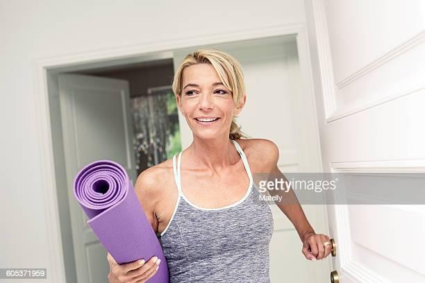 Mature woman at front door carrying yoga mat