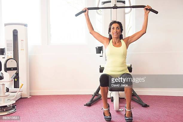 mature woman at gym on exercise machine - エクササイズ用具 ストックフォトと画像