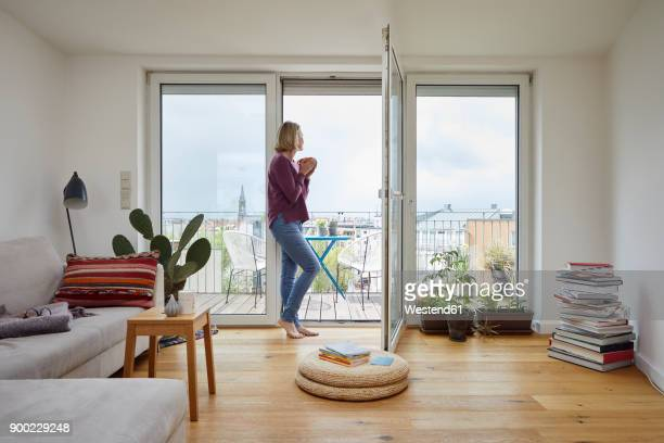 mature woman at home looking out of balcony window - comfortable stock pictures, royalty-free photos & images