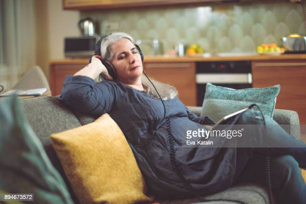 mature woman at home - audio equipment stock pictures, royalty-free photos & images