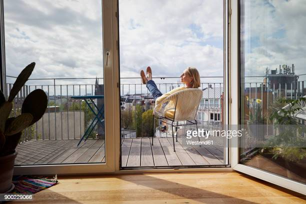 mature woman at home relaxing on balcony - balkon stock-fotos und bilder